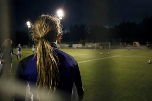 Side view of girl seen through goal post net on soccer fieldの写真素材 [FYI02699446]