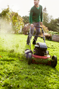 Sweden, Skane, Osterlen, Borrby, Man mowing domestic garden lawnの写真素材 [FYI02699487]