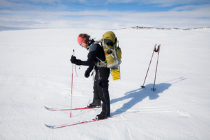 Full length of mature female skier with backpack on snow covered landscapeの写真素材 [FYI02699520]