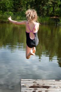 Sweden, Vastra Gotaland, Kallandso, Girl (12-13) jumping intの写真素材 [FYI02699530]