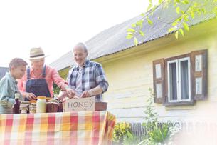 Grandparents and grandson selling honeyの写真素材 [FYI02699543]