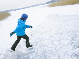 Sweden, Vastergotland, Lerum, Lake Aspen, Boy (10-11) ice-skating on surface of frozen lakeの写真素材 [FYI02699554]
