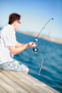 Sweden, Bohuslan, Tjorn, Man fishing from jettyの写真素材 [FYI02699603]