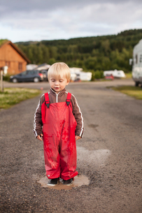 Norway, Brumunddal, Mjosa Camping, Boy (2-3) playing in puddleの写真素材 [FYI02699637]