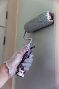 Woman's hand using paint roller on wall at homeの写真素材 [FYI02699668]