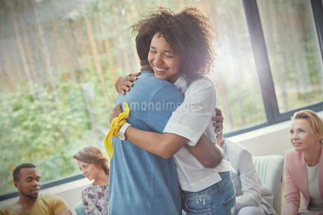 Smiling woman hugging man in group therapy sessionの写真素材 [FYI02699697]