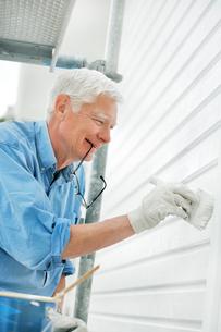 Sweden, Bohuslan, Front view of senior man painting wallの写真素材 [FYI02699715]