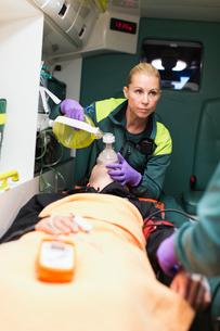 Sweden, Sodermanland, Tumba, Paramedics taking care of patientの写真素材 [FYI02699718]