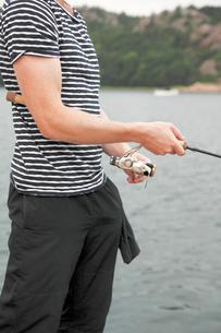 Sweden, Bohuslan, Tjorn, Mid section of young man fishingの写真素材 [FYI02699730]