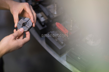Worker examining part in steel factoryの写真素材 [FYI02699764]