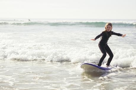 Full length of girl surfing in seaの写真素材 [FYI02699765]