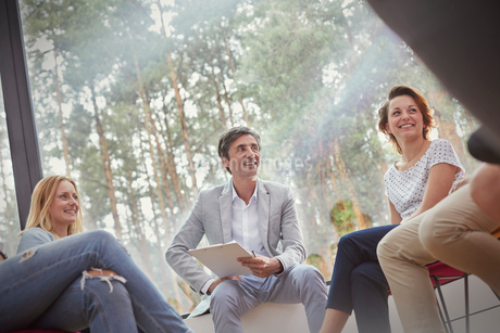 Smiling people talking in group therapy sessionの写真素材 [FYI02699766]