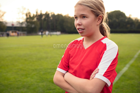 Female soccer player standing with arms crossed on fieldの写真素材 [FYI02699811]