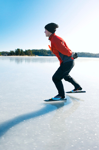 Sweden, Uppland, Loparo, Man ice-skating on frozen lakeの写真素材 [FYI02699814]