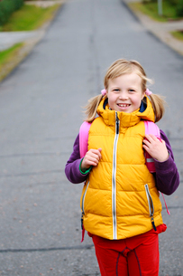 Finland, Keski-Suomi, Jyvaskyla, Front view of girl (6-7) with backpack on empty roadの写真素材 [FYI02699835]