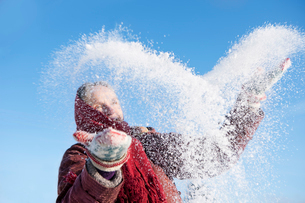 Sweden, Vastergotland, Tarby, Senior woman playing in snowの写真素材 [FYI02699849]