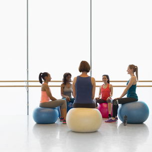 Women on fitness balls in circle in exercise class gym studioの写真素材 [FYI02699908]