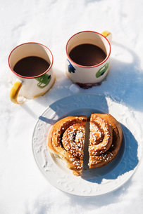 Sweden, Gastrikland, Ockelbo, Halved sweet bun and two coffee cupsの写真素材 [FYI02699921]
