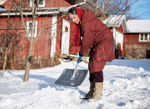 Sweden, Vastergotland, Tarby, Woman clearing off snowの写真素材 [FYI02699952]