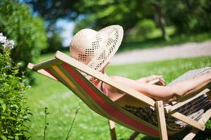 Sweden, Vastergotland, Tarby, Senior woman relaxing on sun cの写真素材 [FYI02699965]