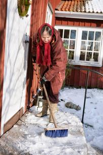Sweden, Vastergotland, Tarby, Senior woman sweeping snowの写真素材 [FYI02699986]