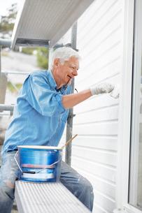 Sweden, Bohuslan, Front view of senior man painting wallの写真素材 [FYI02699989]