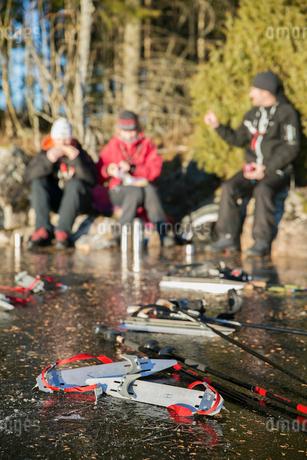 Sweden, Gastrikland, Edsken, Ice skates lying on frozen lake, people in backgroundの写真素材 [FYI02700012]