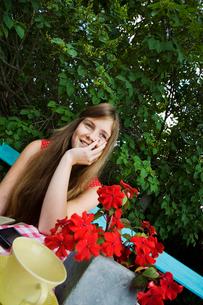 Sweden, Dalarna, Portrait of girl (14-15) sitting on benchの写真素材 [FYI02700050]