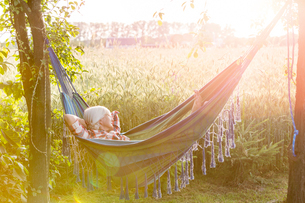 Serene woman napping in hammock next to sunny rural wheat fieldの写真素材 [FYI02700056]