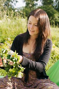 Sweden, Uppland, Vallentuna, Young woman making flowery wreaの写真素材 [FYI02700062]