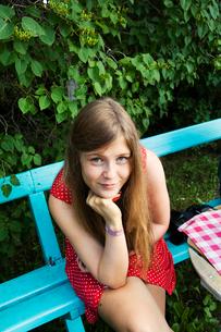 Sweden, Dalarna, Portrait of girl (14-15) sitting on benchの写真素材 [FYI02700068]
