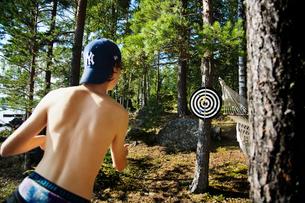 Sweden, Dalarna, Boy (14-15) playing darts outdoorsの写真素材 [FYI02700070]