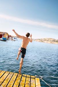 Sweden, Bohuslan, Tjorn, rear view of man jumping into waterの写真素材 [FYI02700072]