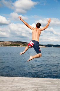 Sweden, Bohuslan, Tjorn, Rear view of man jumping into waterの写真素材 [FYI02700081]