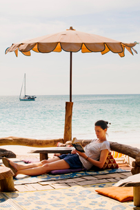 Thailand, Koh Lanta, Woman relaxing on beachの写真素材 [FYI02700107]