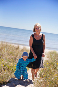 Sweden, Gotland, Faro, Skalasand, Mother and son (2-3) walking along beach footpathの写真素材 [FYI02700108]