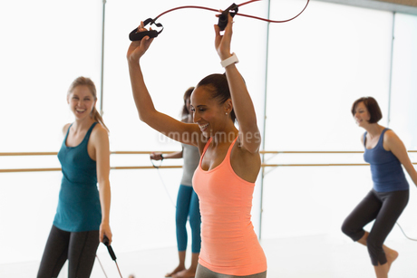 Smiling women jumping rope in exercise class gym studioの写真素材 [FYI02700146]