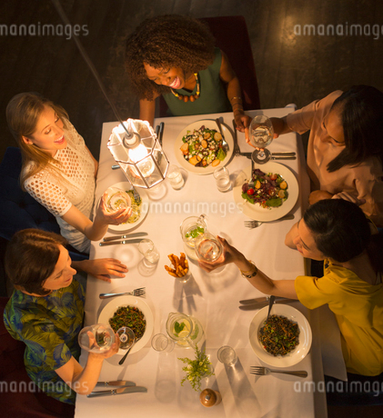 Smiling women friends toasting white wine glasses dining at restaurant tableの写真素材 [FYI02700152]