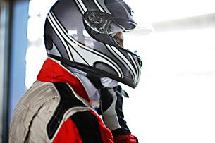 Racer tying on helmet in garageの写真素材 [FYI02700174]