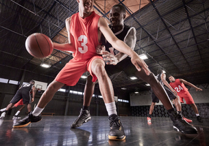Young male basketball players playing game on court in gymnasiumの写真素材 [FYI02700204]