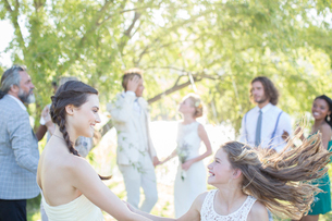 Bridesmaid and girl dancing during wedding reception in domestic gardenの写真素材 [FYI02700227]