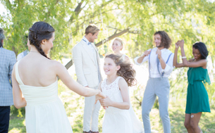 Bridesmaid and girl dancing during wedding reception in domestic gardenの写真素材 [FYI02700236]