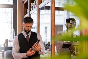 Well-dressed bartender examining whiskey bottleの写真素材 [FYI02700278]