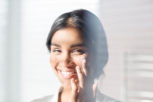 Close up portrait smiling woman applying moisturizer to cheekの写真素材 [FYI02700285]