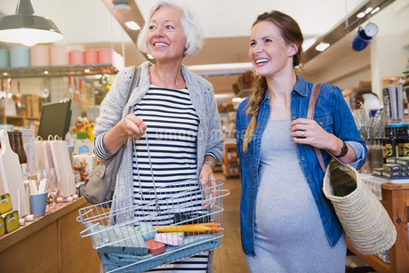 Smiling pregnant woman and mother shopping in shopの写真素材 [FYI02700286]