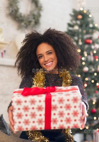 Portrait smiling woman giving Christmas giftの写真素材 [FYI02700298]