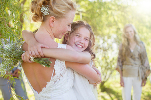 Bride embracing bridesmaid at wedding reception in domestic gardenの写真素材 [FYI02700304]