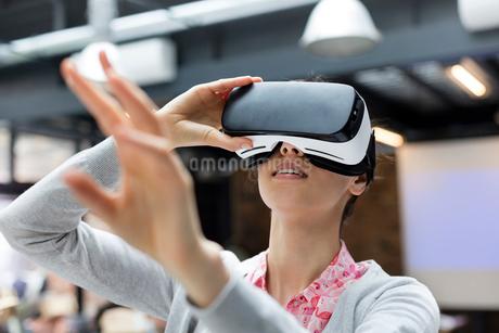 Woman trying virtual reality simulator glasses glasses reachingの写真素材 [FYI02700313]