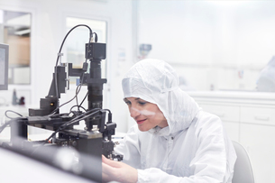 Female engineer in clean suit using equipment in fiber optics research and testing laboratoryの写真素材 [FYI02700391]