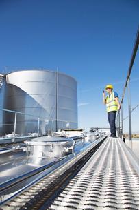Worker using walkie-talkie on platform above stainless still milk tankerの写真素材 [FYI02700396]